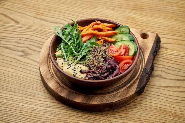 Вегетарианский салат с киноа, запеченной свеклой и морковью, хумусом и свежими овощами в глиняной тарелке на деревянном столе