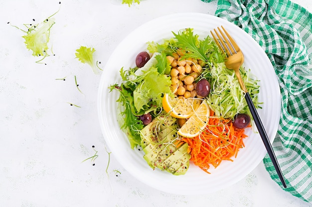 Vegetarian salad buddha bowl dish with chickpea, avocado, cucumber, carrot, chia seeds, lettuce salad and olives.