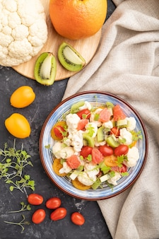 Vegetarian salad of cauliflower cabbage, kiwi, tomatoes, microgreen sprouts on black concrete background and linen textile. top view, flat lay,