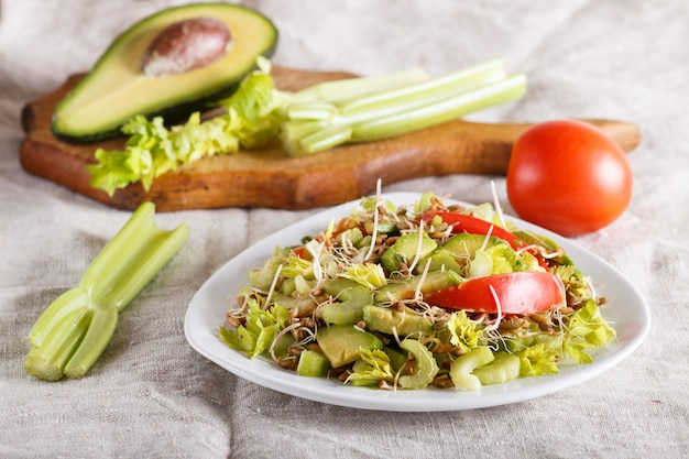 Vegetarian salad of celery, germinated rye, tomatoes and avocado on linen tablecloth.