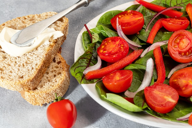 Vegetarian salad of cherry tomatoes, spinach, red onions and bell peppers with butter. on a gray background. copy space.