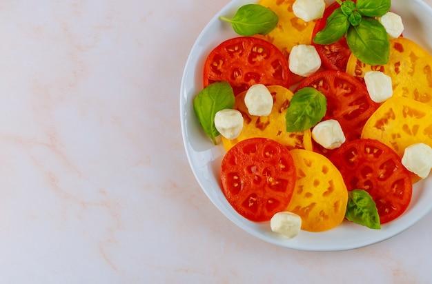 Вегетарианский салат из томатов, моцареллы и базилика вид сверху