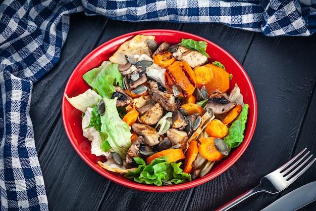 ニンジン、キノコ、レタスの暗い木製の表面にオレンジボウルのベジタリアンサラダ