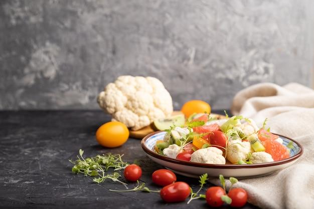 Вегетарианский салат из цветной капусты, киви, помидоры, ростки микрогрин на черном фоне конкретных. вид сбоку, копия пространства.