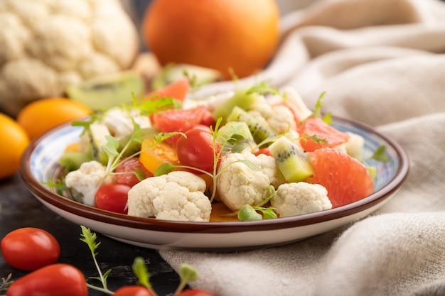 Вегетарианский салат из цветной капусты, киви, помидоры, ростки микрогрин на черном фоне конкретных. вид сбоку, выборочный фокус.