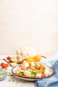Вегетарианский салат из капусты цветной капусты, киви, помидоры, ростки microgreen на сером фоне деревянных. вид сбоку, выборочный фокус, копия пространства.