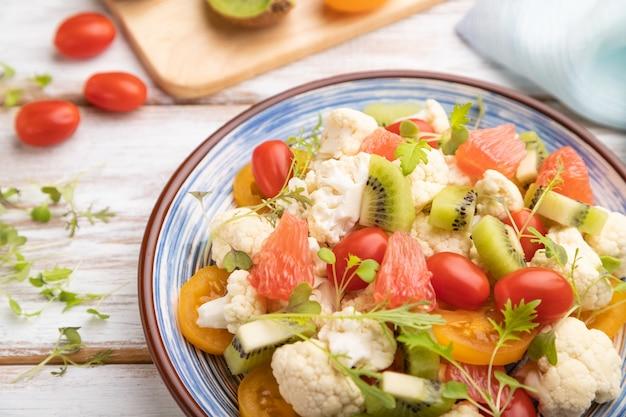 Вегетарианский салат из капусты цветной капусты, киви, помидоры, ростки microgreen на сером фоне деревянных. вид сбоку, выборочный фокус.