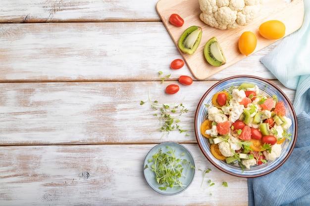 Вегетарианский салат из капусты цветной капусты, киви, помидоры, ростки microgreen на сером фоне деревянных. вид сверху, копия пространства.