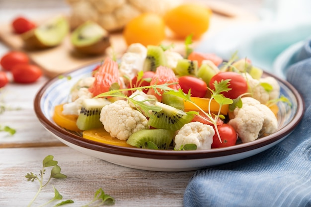 Вегетарианский салат из цветной капусты, киви, помидоров, ростков микрозелени на белом деревянном фоне и синей льняной ткани. вид сбоку