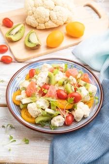 Вегетарианский салат из цветной капусты, киви, помидоров, ростков микрозелени на белом
