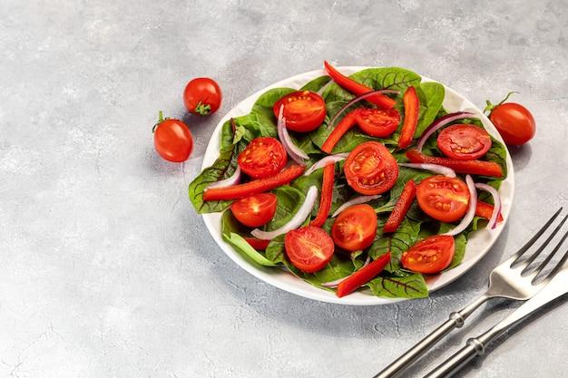 체리 토마토, 시금치, 적 양파, 피망과 버터의 채식 샐러드. 회색 배경. 공간을 복사하십시오.