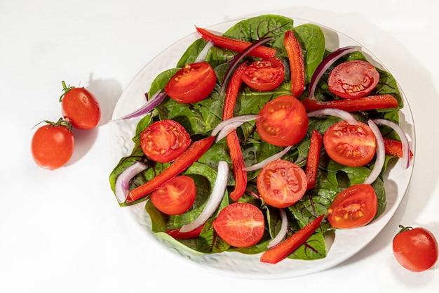 체리 토마토, 시금치, 적 양파, 피망과 버터의 채식 샐러드. 흰색 배경에. 격리. 공간을 복사하십시오.