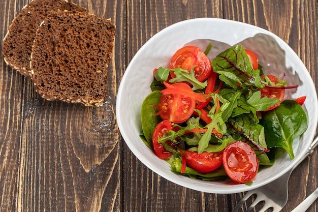 체리 토마토, 시금치, 적 양파, 피망과 버터의 채식 샐러드. 나무 배경. 공간을 복사하십시오.