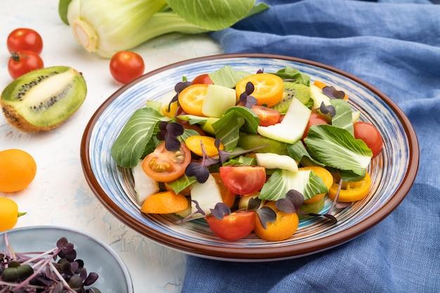흰색 콘크리트 표면에 pac choi 양배추, 키위, 토마토, 금귤, microgreen 콩나물과 파란색 리넨 섬유의 채식 샐러드