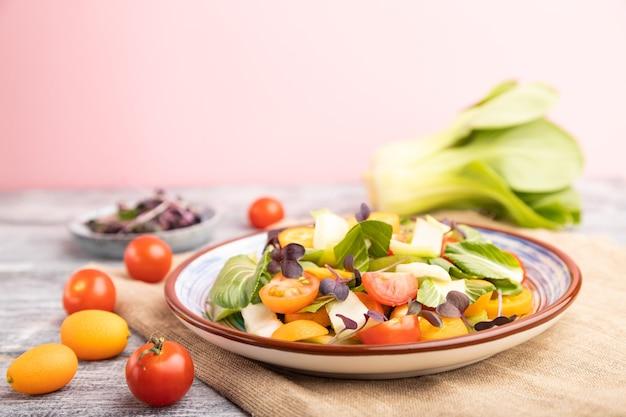 Pac choi 양배추, 키위, 토마토, 금귤, 회색 및 분홍색 표면과 린넨 직물에 마이크로 그린 콩나물의 채식 샐러드