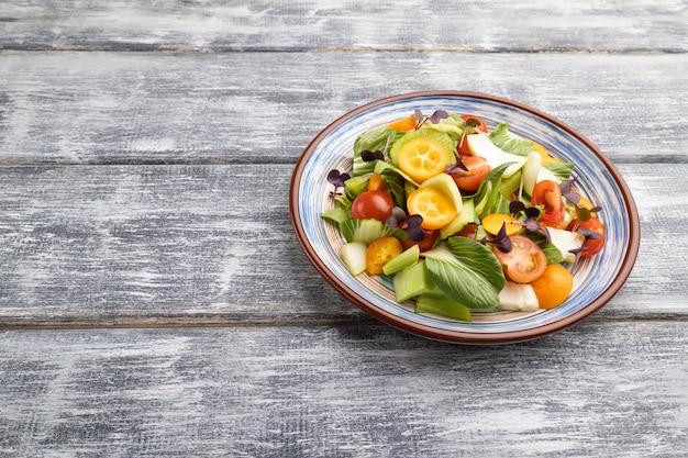 パックチョイキャベツ、キウイ、トマト、キンカン、灰色の木製の背景にマイクログリーンスプラウトのベジタリアンサラダ。