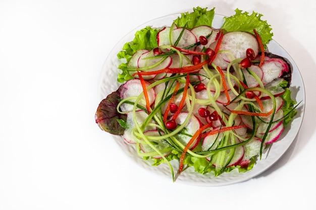 무, 시금치, 적 양파, 피망, 오이의 채식 샐러드. 밝은 배경에. 공간을 복사하십시오.