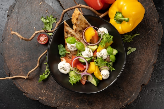 野菜、玉ねぎ、チェリートマト、赤と黄色のピーマンと緑のモッツァレラチーズのベジタリアンサラダ