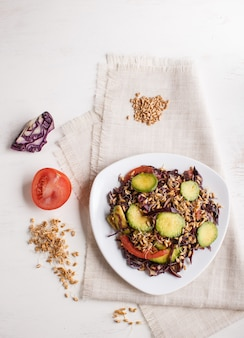 Vegetarian salad of purple cabbage, germinated wheat, tomatoes and avocado on linen tablecloth