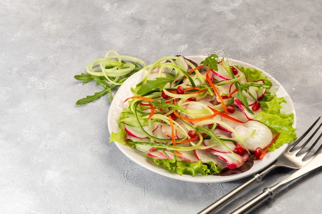 Vegetarian salad of radish, spinach, red onion and bell pepper and cucumber. on a light background. copy space.