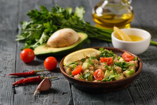 黒い木製のテーブルにアマランスの種子、アボカド、チェリートマトのベジタリアンサラダ。