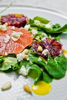 Vegetarian salad with arugula, grapefruit, red oranges, nuts and tofu cheese.