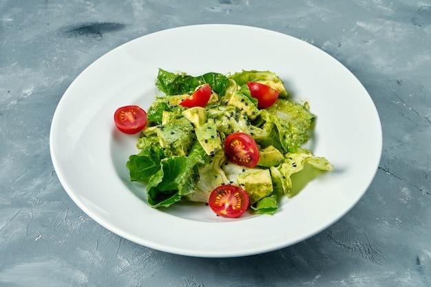 Вегетарианский салат с авокадо, листьями салата и помидорами черри в белой тарелке на бетонной поверхности