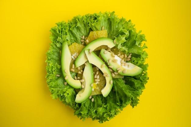 黄色の背景にアボカド、レタスの葉、オレンジと松の実のベジタリアンサラダ。上面図。