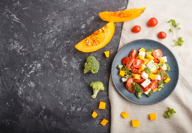 Vegetarian salad with broccoli, tomatoes, feta cheese, and pumpkin on a blue ceramic plate