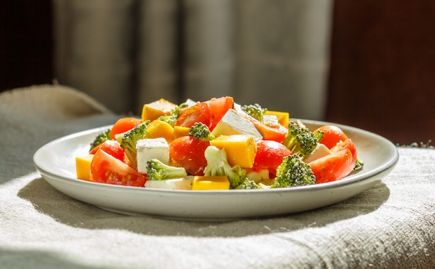 Vegetarian salad with broccoli, tomatoes, feta cheese, and pumpkin on white ceramic plate on linen textile,