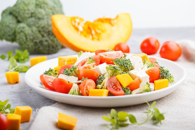 Vegetarian salad with broccoli, tomatoes, feta cheese, and pumpkin on white ceramic plate