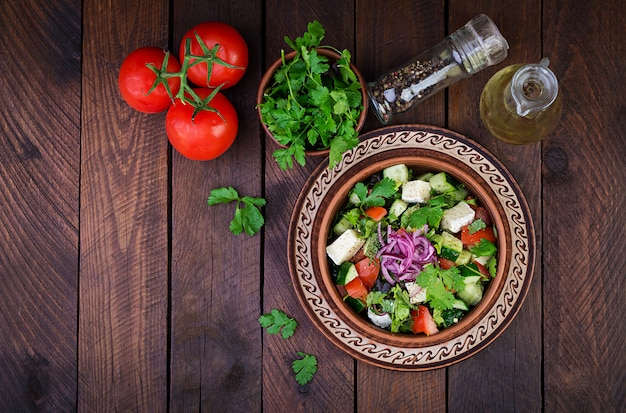 Vegetarian salad with cherry tomato, brie cheese, cucumber, cilantro and red onion