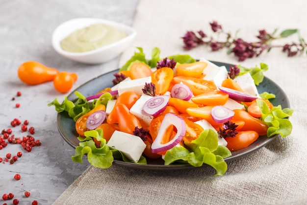 Vegetarian salad with fresh grape tomatoes, feta cheese, lettuce and onion, top view.