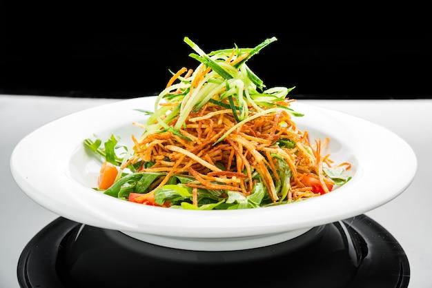 フライドポテトチップと皿にルッコラのベジタリアンサラダ