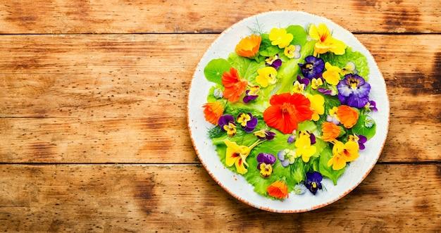 녹색과 식용 꽃을 곁들인 채식 샐러드. 꽃이 든 신선한 여름 샐러드. 복사 공간이 있는 평면