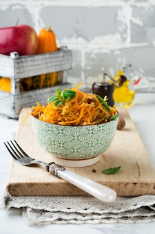 Вегетарианский салат с тыквой, яблоками и изюмом на светлой поверхности