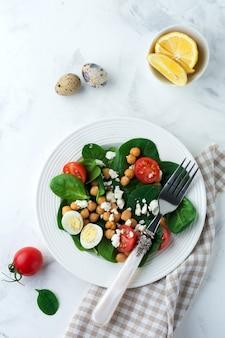 Вегетарианский салат со шпинатом, нутом, помидорами черри, яйцом и сыром фета и лимоном на светлом фоне.