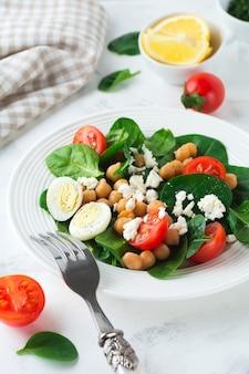 밝은 표면에 시금치, 병아리 콩, 체리 토마토, 계란 및 페타 치즈와 레몬을 곁들인 채식 샐러드