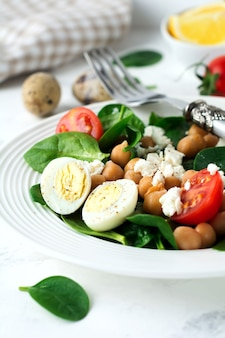 Vegetarian salad with spinach, chickpeas, cherry tomatoes, egg and feta cheese and lemon on a light surface. selective focus