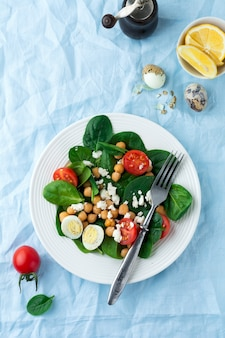 Vegetarian salad with spinach, chickpeas, cherry tomatoes, egg and feta cheese and lemon on a light surface
