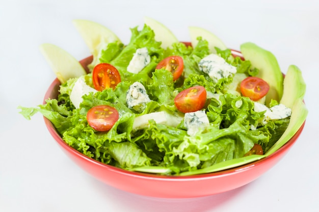 Vegetarian salad with tomatoes, cheese, lettuce. vegetables in the red bowl. delishes food.