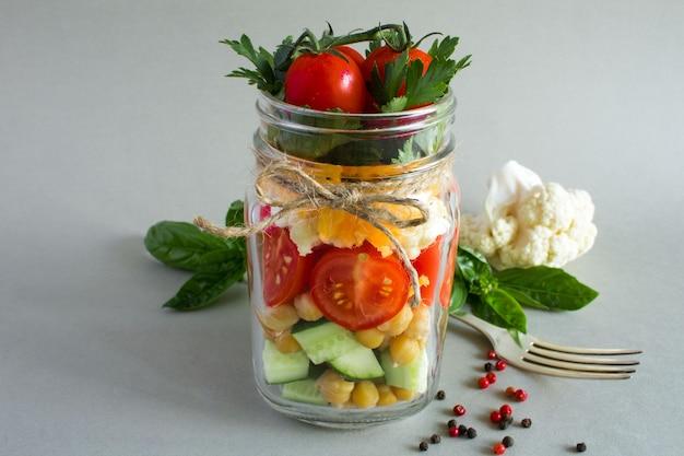 灰色のガラス瓶に野菜とひよこ豆のベジタリアンサラダ