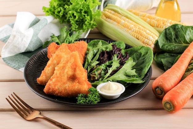トマトソースとマヨネーズの三角形のベジタリアンサムサ(サモサ)。 risolessayurとしてインドネシアで人気があります。 (ベジタブルリッソール)