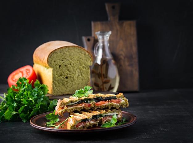 Вегетарианский сэндвич панини с листьями шпината, помидорами и сыром на темном столе. тост с сыром.