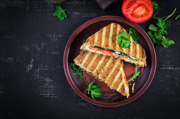 Vegetarian sandwich panini with spinach leaves, tomatoes and cheese on a dark table. toast with cheese. top view, overhead, copy space