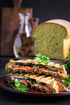Vegetarian sandwich panini with spinach leaves, tomatoes and cheese on a dark table. toast with cheese.
