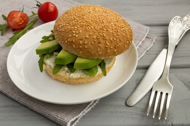 Вегетарианский бутерброд с авокадо и рукколой на серой салфетке