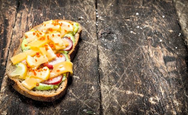 나무 테이블에 치즈, 무, 신선한 허브 소스와 함께 채식 샌드위치.