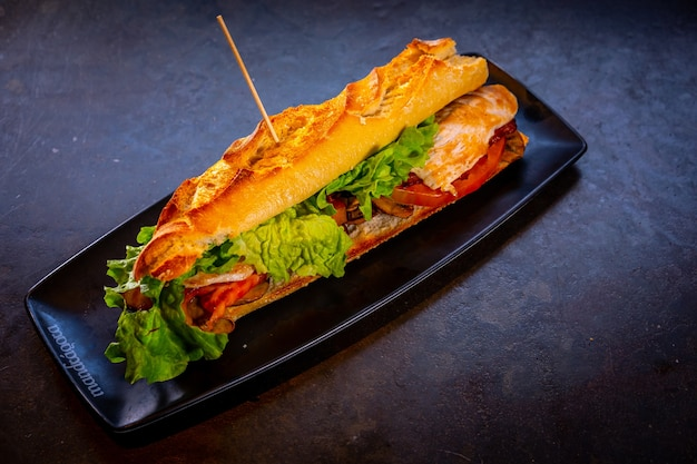 Vegetarian sandwich with chicken on a black background, on a white plate