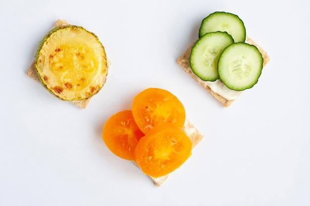 ベジタリアンは、白い背景の無愛想なパンに野菜をサンドイッチします